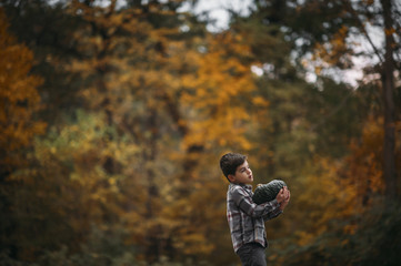 Side view of boy carrying pumpkin at park