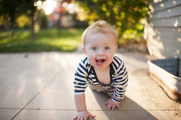 Portrait of cute baby boy crawling at backyard