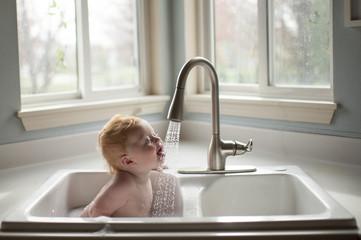Baby boy taking bath while sitting in kitchen sink