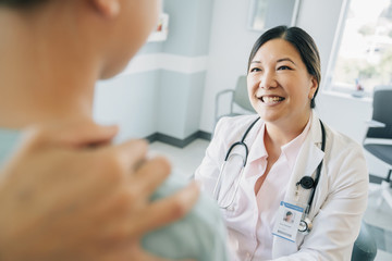 Cheerful pediatrician looking at girl in medical examination room