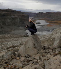 Side view of female hiker holding camera while crouching on rock