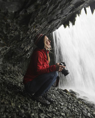 Cheerful female hiker looking at waterfall while holding camera