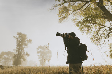 Hiker photographing with camera while standing on field