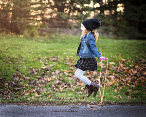 Side view of girl jumping rope on footpath at park during autumn