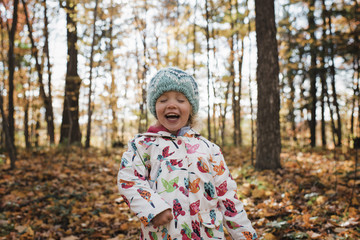 Cute girl with eyes closed laughing while standing at forest