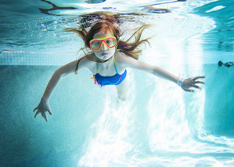 Portrait of girl swimming underwater in pool