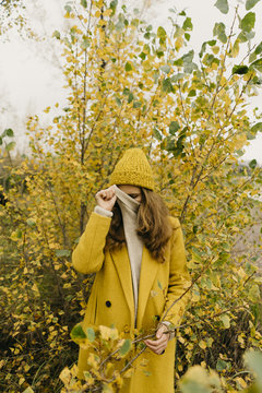 Woman covering face while standing against plants during autumn