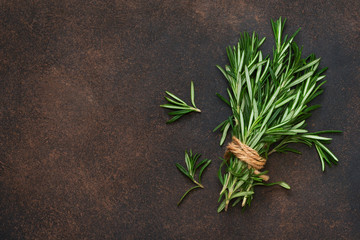 A fresh bunch of rosemary on a brown concrete background. Organic food background.