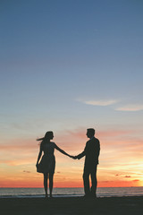 Couple holding hands while standing on beach during sunset