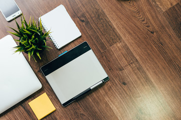 on the wooden floor is a laptop for work, a graphic tablet, a notebook, a smartphone and a potted plant