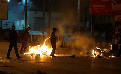 Riot police clash with protesters during demonstrations against rising prices and tax increases, in Tunis