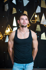 Handsome man in black tank top, posing, fashion portrait