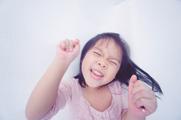 Happy funny little asian girl raise hand and glad and lying to the floor in restaurant.