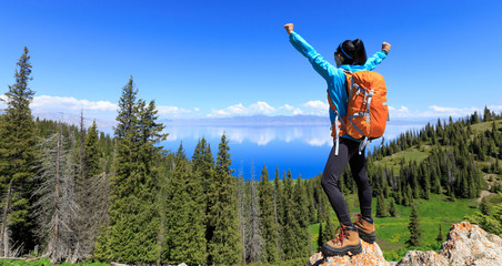 successful Hiker outstretched arms stand at cliff edge on mountain top Wall mural