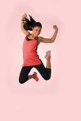 young happy and beautiful girl jumping crazy excited in female sport fitness concept isolated on pink background wearing red sportswear