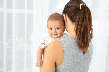 Young mother with cute baby at home