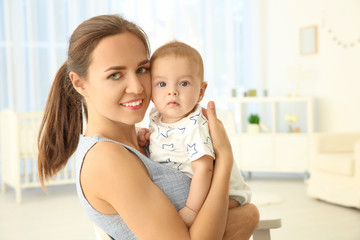 Portrait of young mother with cute baby at home