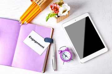 Composition with word ENGAGEMENT, notebook, clock and tablet computer on white wooden background