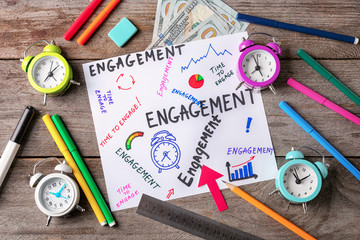 Sheet of paper with written words ENGAGEMENT, clocks and markers on wooden background