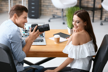 Professional photographer taking picture of beautiful young model in office