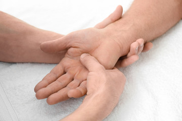 Physiotherapist giving hand massage to senior patient, closeup
