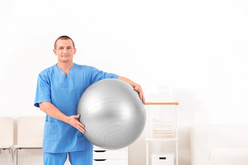 Young physiotherapist with ball in rehabilitation centre
