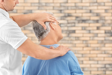 Physiotherapist working with patient on brick wall background