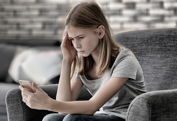 Sad teenage girl with smartphone at home