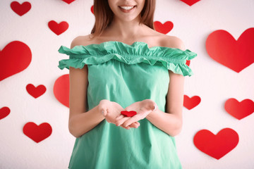 Romantic young woman with small felt heart near wall decorated for Valentine's Day