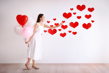 Romantic young woman with balloons near wall decorated for Valentine's Day