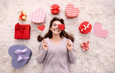 Beautiful young woman with gifts for Valentine's Day lying on floor at home