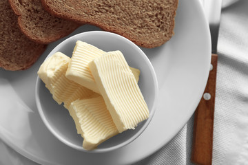 Composition with fresh butter and bread on table