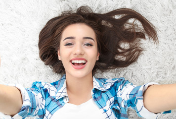 Beautiful smiling woman taking selfie while lying on carpet at home