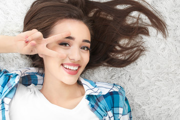 Portrait of beautiful woman showing victory gesture while lying on carpet at home