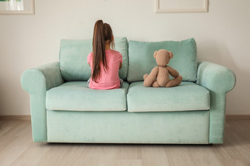 Little girl with teddy bear sitting on sofa at home. Child autism