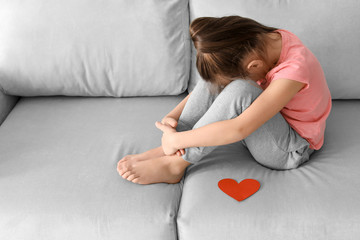 Little girl crying near paper heart at home. Child autism