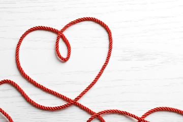 Heart made of red rope on white wooden background