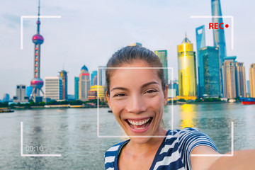 Happy China travel selfie Asian tourist woman vlogging online recording videoblog vlog video. Smiling young girl holding camera phone at the Bund at Shanghai's skyline of skycrapers.