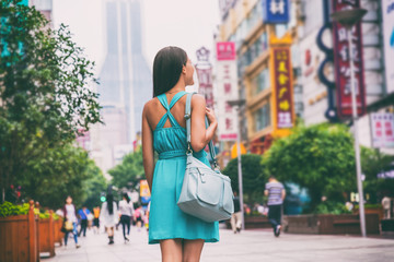 Shanghai city travel lifestyle shopping woman walking on Nanjing Road shop street, China, Asia. Asian girl with purse on urban adventure, famous chinese attraction landmark.