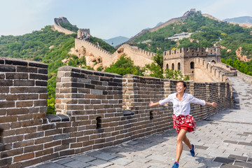Wall Mural - Happy cheerful joyful tourist woman at Great Wall of china having fun on travel smiling laughing and dancing during vacation trip in Asia. Girl visiting and sightseeing Chinese destination in Badaling