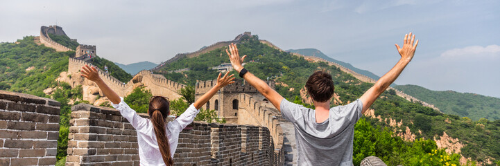China travel people winning of joy in Asia on Great Wall, Beijing, chinese landmark. Young couple tourists with arms up in happiness winners visiting Great Wall panorama landscape crop for background.