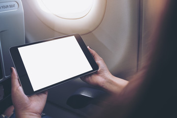 Mockup image of a woman holding and looking at black tablet pc with blank white desktop screen next to an airplane window with clouds and sky background