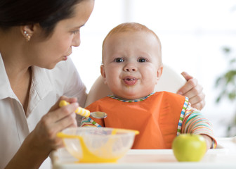 Mom feeds her kid. Baby is crying, capricious and refusing to eat