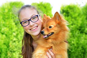 Portrait of happy young girl with her pet dog in nature.