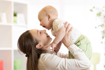 Positive baby and mom. Young mother plays with her little son.