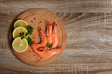 Shrimps with slices of lemon on cutting board.