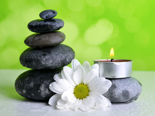 Stack of Zen pebble stones with flower and candle. Spa and healthcare concept.