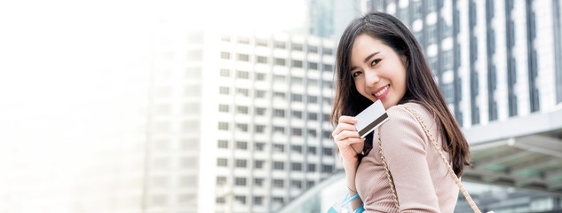 Smiling Asian woman showing credit card