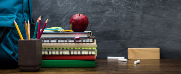 Stack of books, colorful stationery and education supplies on wooden table
