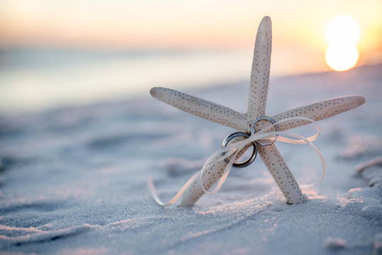 Wedding Rings tied to a Starfish Stuck in the Sand on the Beach with the Sunset in the Background